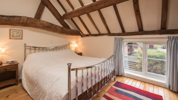 The first-floor double bedroom with original exposed beams